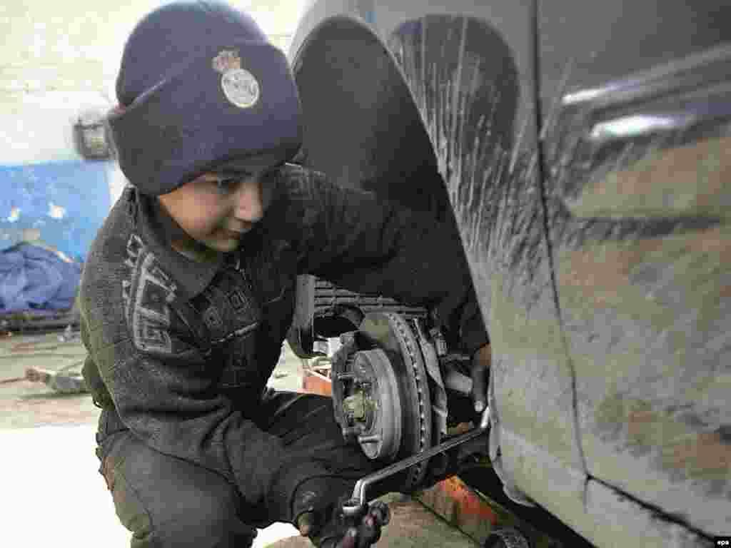 A 12-year-old boy works in a garage in Baghdad.