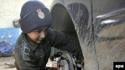 طفل عراقي يعمل في ورشة تصليح السيارات