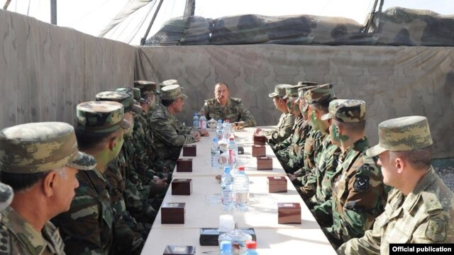 Azerbaijani President Ilham Aliyev (center) talks to soldiers serving in the Agdam district east of Nagorno-Karabakh on August 6.