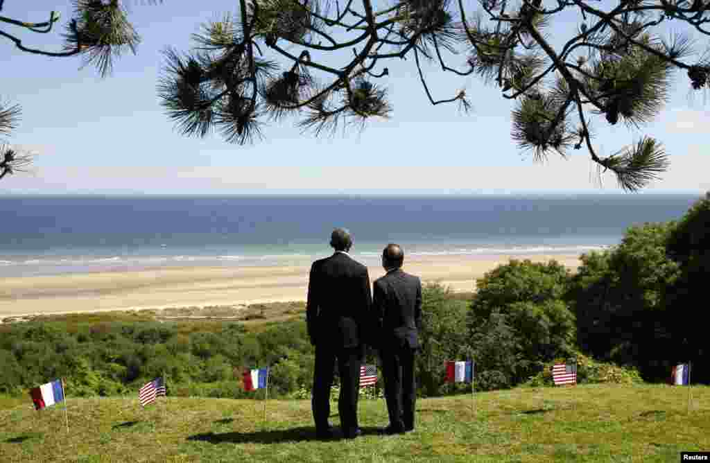U.S. President Barack Obama and French President Francois Hollande look out over Omaha Beach as they participate in the 70th French-American Commemoration D-Day Ceremony at the Normandy American Cemetery and Memorial in Colleville-sur-Mer.