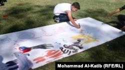 طفل يرسم لوحة في معرض يستنكر الإساءة للأديان أقيم في الموصل في 19/9/2012