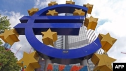A giant logo of the euro currency stands in front of the European Central Bank in the banking district of Frankfurt, Germany.