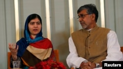 Nobel Peace Prize laureate Malala Yousafzai (L) speaks next to Kailash Satyarthi during a news conference in Oslo on December 9.