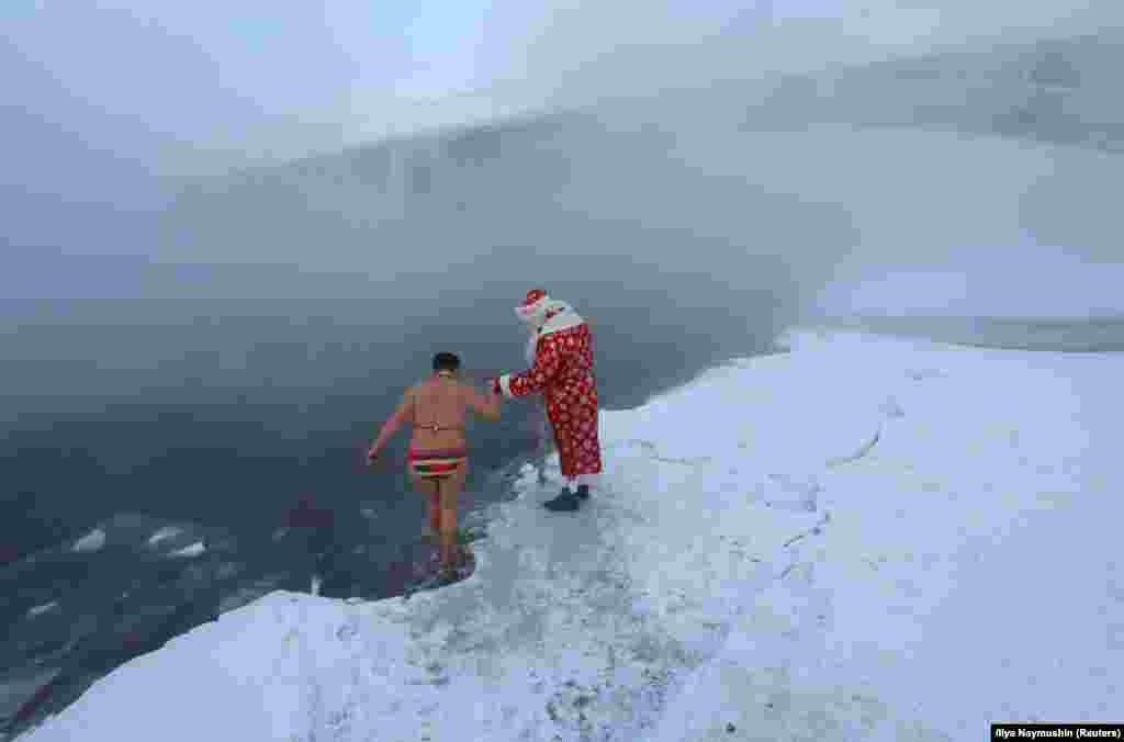 A man dressed as Ded Moroz, the Russian equivalent of Santa Claus, helps a member of the Cryophile amateur winter swimmers club walk into the icy waters of the Yenisei River with the air temperature at about minus 26 degrees Celsius, in Krasnoyarsk, Russia. (Reuters/Ilya Naymushin)