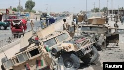 FILE: Afghan National Army (ANA) soldiers inspect damaged army vehicles after a suicide attack in Lashkar Gah,.