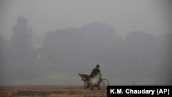 A cyclist pushes his laden bike through smog, in Lahore on November 21