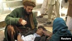 Маці каля параненага сына пасьля тэракту ў правінцыі Кундуз у Аўганістане.