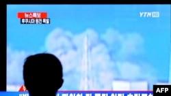 Житель Южной Кореи смотрит телерепортаж о взрыве на японской АЭС 12 марта