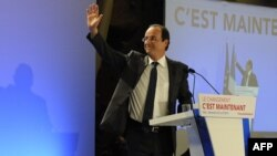 Socialist Party candidate Francois Hollande waves on stage following early vote results in Tulle.