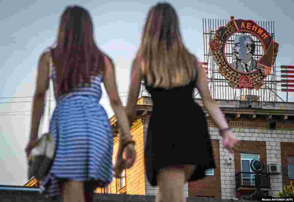 Russian girls pass in front of a building with a display of Soviet state founder Vladimir Lenin Order in Volgograd (formerly Stalingrad). (AFP/Mladen Antonov)