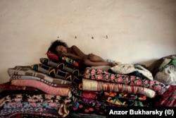 A girl naps on a pile of mats in a Romany village near Bukhara in 2010.