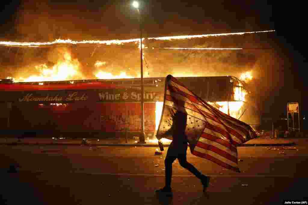 Demonstrant sa američkom zastavom okrenutom naopako u znak protesta, hoda pored goruće zgrade 28. maja u Minneapolisu tokom protesta zbog smrti 46-godišnjeg Afroamerikanca Georgea Floyda. Floyd je preminuo 25. maja u bolnici. Na videu u kojem se prikazuje njegovo hapšenje vidi se bijeli policajac kako drži nogu na njegovom vratu dok Floyd govori da ne može disati.