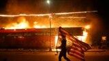 <p>Demonstrant sa američkom zastavom okrenutom naopako u znak protesta, hoda pored goruće zgrade 28. maja u Minneapolisu tokom protesta zbog smrti 46-godišnjeg Afroamerikanca Georgea Floyda. Floyd je preminuo 25. maja u bolnici. Na videu u kojem se prikazuje njegovo hapšenje vidi se bijeli policajac kako drži nogu na njegovom vratu dok Floyd govori da ne može disati.</p>