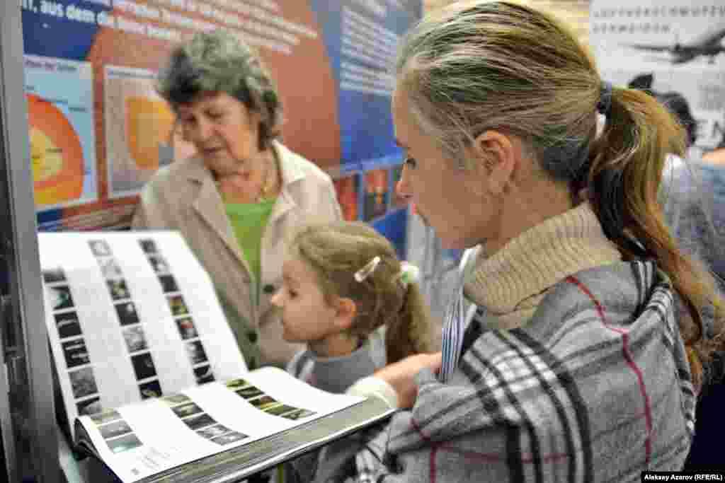 Эта семья (бабушка, внучка и тетя девочки) листают альбом на немецком языке, рассказывающий о недрах Земли.