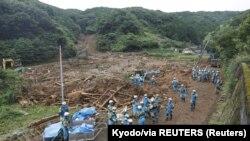 Сотрудники полиции разыскивают пропавших людей на месте оползня, вызванного сильным дождем в городе Цунаги, префектура Кумамото, на юге Японии