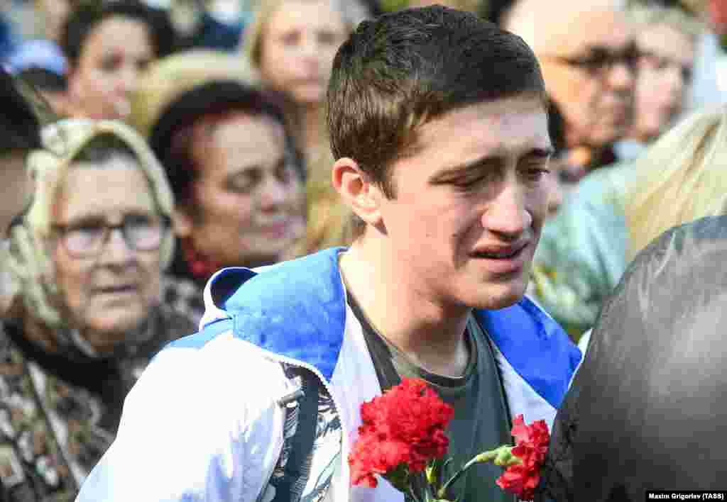 Молодой человек около импровизированного мемориала возле Керченского политехнического колледжа