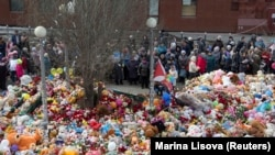 People stand near toys, flowers, balloons, and other items as they gather to commemorate the victims of a shopping mall fire on the day of national mourning in Kemerovo on March 28.