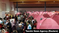 People are seen sheltering at a stadium in Red Crescent tents after a flooding in Golestan province, Iran, March 24, 2019.