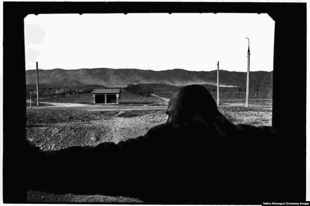 A passenger watches the landscape as his train rolls through Uplistsikhe.