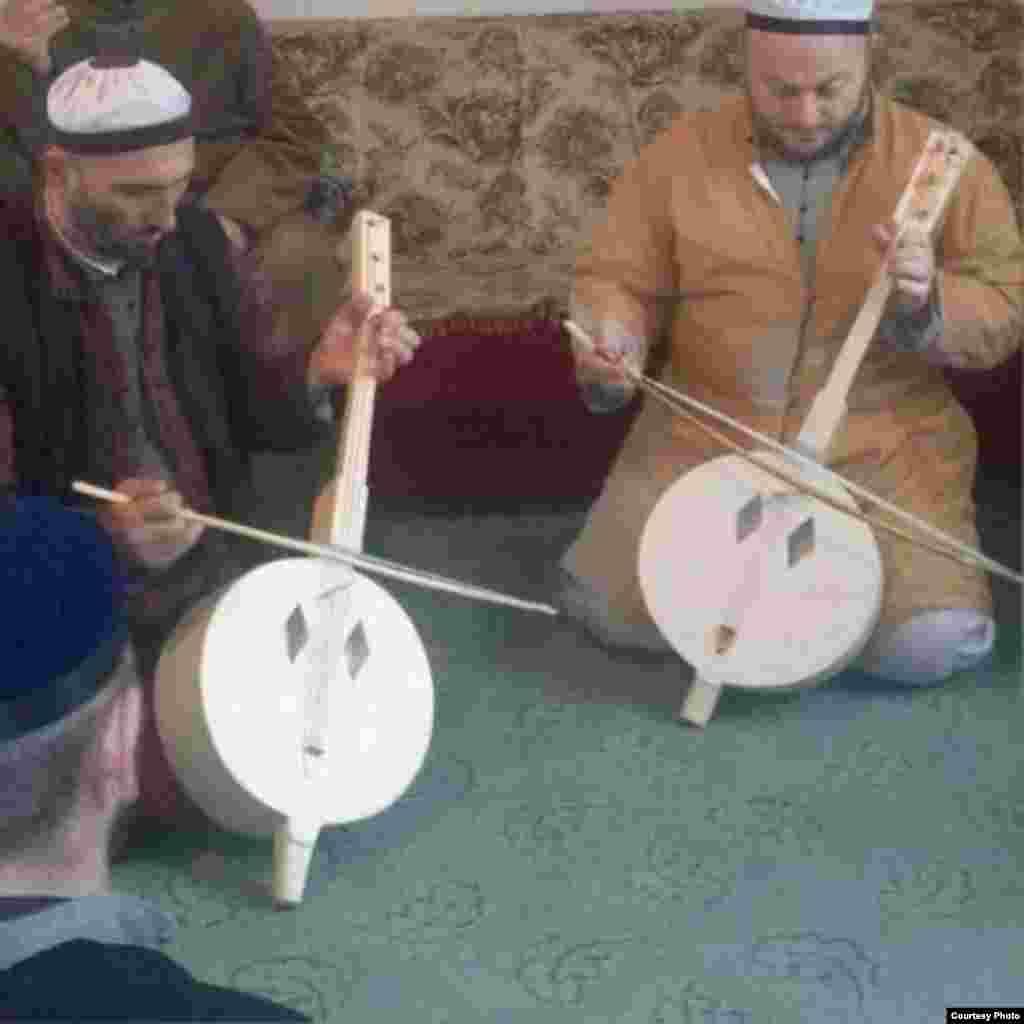 Мужчины играют на чеченском народном инструменте, который используется при исполнении религиозных песнопений.