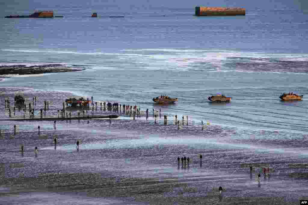 FRANCE -- WWII enthusiasts walk near DUKW (colloquially known as Duck), a six-wheel-drive amphibious modification of the 2 1/2-ton CCKW trucks used by the U.S. military, on the beach of Asnelles, in Normandy, on June 6, 2019