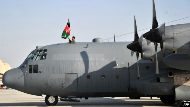 A member of the Afghan Air Force raises the national flag on top of a C-130 transport aircraft at Kabul's international airport on October 9, 2013.