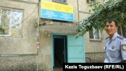 Участковый инспектор Сарсен Жунисбаев у подъезда в жилом доме, где находится полицейский участок. Алматы.