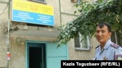 Учаскелік инспектор Сәрсен Жүнісбаев учаскелік полиция пункті орналасқан көпқабатты тұрғын үйдің алдында тұр. Алматы, 18 тамыз 2013 жыл.