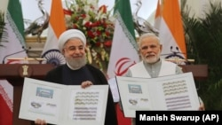 Indian Prime Minister Narendra Modi, right, with Iranian President Hassan Rouhani release a postal stamp commemorating growing economic and trade ties between the two nations in New Delhi, February 17, 2018