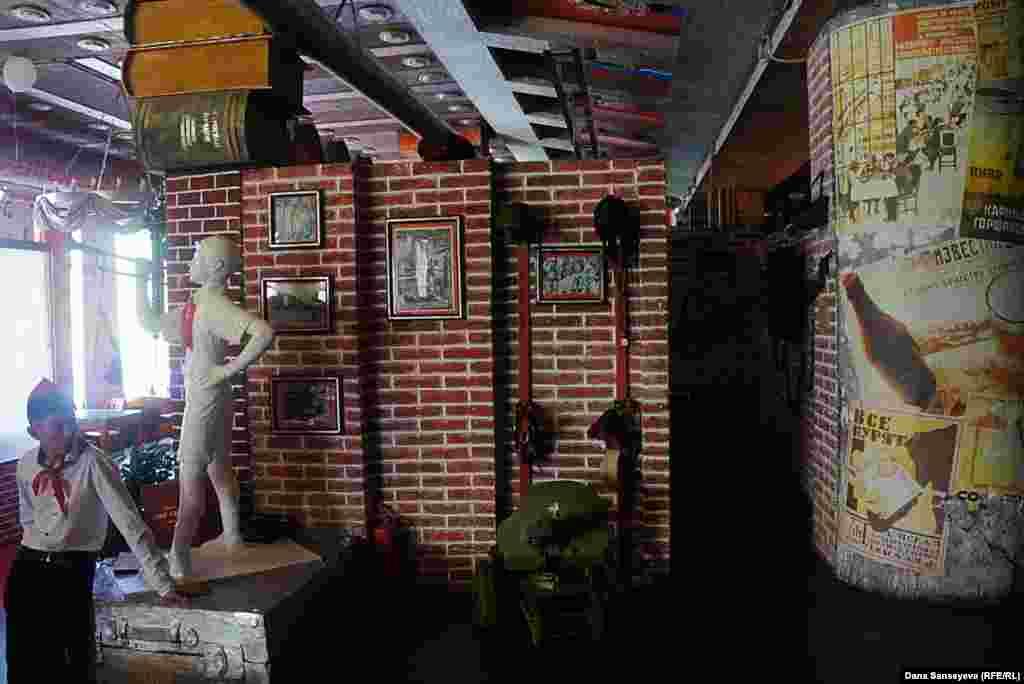 """Официант в кафе """"Эпоха"""" в форме пионера. Официантки здесь одеты в советскую школьную форму с белым фартуком. На стенах висят оружие и военное оборудование с надписями о тех, кому предметы принадлежали в советское время."""