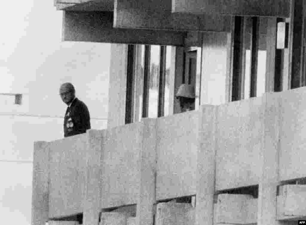 A Palestinian terrorist (right) appears on a balcony at the Israeli apartment watching an official at the Olympic village at the height of the crisis on September 5, 1972.