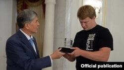 Президент Атамбаев жаҳон чемпиони Поветкинга Манас рамзи туширилган сувенирни топширмоқда.