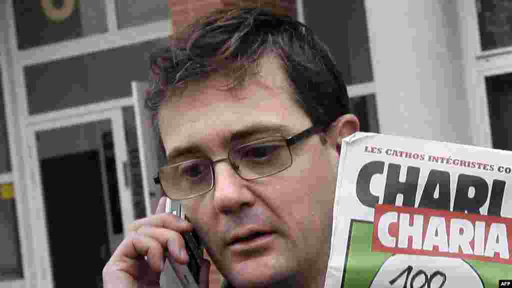Charlie Hebdo's publisher, known only as Charb, uses his cell phone as he shows a special edition of the magazine in Paris on November 2, 2011.