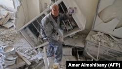 Мешканець містечка Кафр-Батна у Східній Гуті показує фото родини, врятоване з руїн його дому після повітряного удару, 1 березня 2018 року
