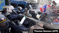 Riot police spray tear gas on demonstrators during clashes on the Champs-Elysees.