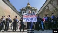 Фото более позднего периода. Украинка держит плакат с лозунгом «Московский патриархат – это проклятие для Украины!» во время протеста перед кордоном милиции возле входа в Киево-Печерскую лавру. Киев, 13 августа 2014 года