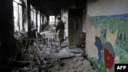A Ukrainian serviceman walks through a destroyed school in the village of Pisky near Donetsk late last year.