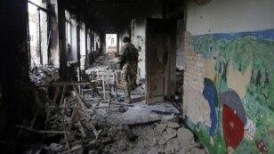 A Ukrainian serviceman walks through a destroyed school in the village of Pisky near Donetsk late last year.