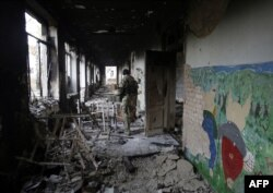 A Ukrainian serviceman walks through a destroyed school near Donetsk. (file photo)