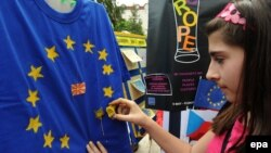 Macedonia -- A girl paints the stars of the EU flag on a t-shirt during the celebration of European day in the center of Skopje, 08May2010