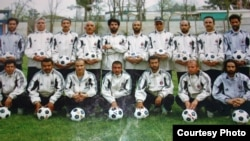 Mohammad Isaq (top right) poses with members of the Sabawoon 1999 soccer team at Ghazi Stadium in Kabul.