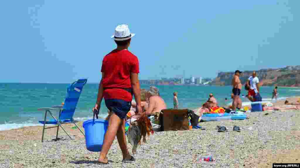 Школьник на каникулах продает рыбу на пляже отдыхающим