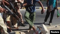 Libyan rebel fighters step on a picture of Muammar Qaddafi at a checkpoint in Tripoli on August 22.