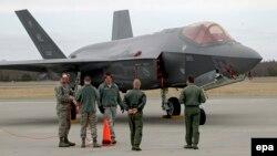 Американские военнослужащие рядом с истребителем-бомбардировщиком F-35.