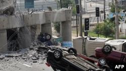 Overturned cars lie on a collapsed bridge in the capital, Santiago, after the 8.8-magnitude earthquake on February 27.