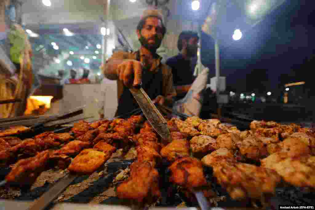 A man sells roasted chicken in Peshawar, Pakistan. (EPA-EFE/Arshad Arbab)