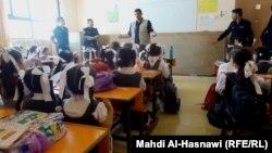 أحد عناصر دائرة الدفاع المدني يلقي محاضرة على طالبات في مدرسة بمحافظة ذي قار