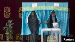 Избиратели выходят из кабинок для голосования на участке в селе Туздыбастау. Алматинская область, 26 апреля 2015 года.