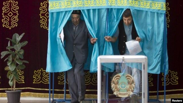 Мужчины выходят из кабинок для голосования во время досрочных президентских выборов. Село Туздыбастау Алматинской области, 26 апреля 2015 года.