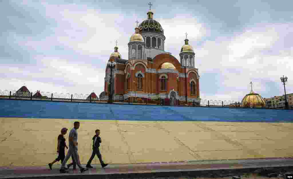 People walk past the Church of the Intercession of the Holy Virgin on a Dnipro River embankment painted in the colors of the Ukrainian national flag in Kyiv on June 26. (epa/Roman Pilipey)